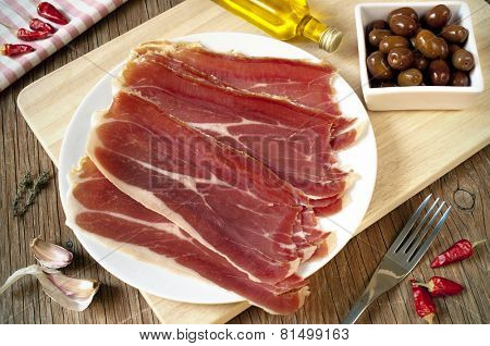 a plate with spanish serrano ham and a bowl with black olives served as tapas