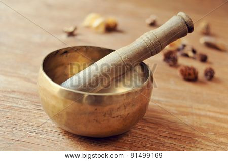 closeup of a tibetan singing bowl with its mallet on a table with dried flowers