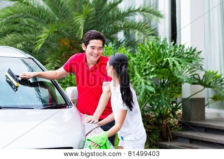Asian couple cleaning windscreen or windshield and headlamps while car wash