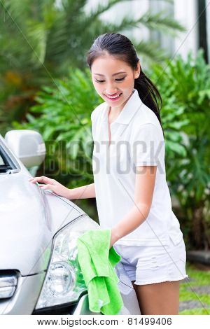 Asian woman cleaning headlamp at car wash