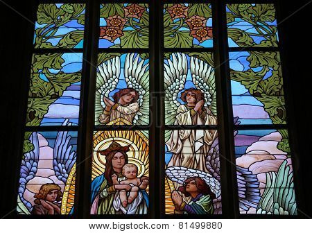 KUTNA HORA, CZECH REPUBIC - AUGUST 23, 2014: Virgin Marry surrounded by angels. Art Nouveau stained glass window in Saint Barbara Church in Kutna Hora, Czech Republic.