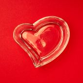 picture of pacemaker  - Heart made of glass lying on the bright red surface composition - JPG