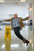 pic of slip hazard  - African American businessman slipping on wet floor inside office building - JPG