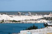 stock photo of silos  - Limestone Mining on an Island with storage silos and ship waiting to be loaded and deep blue Ocean Water - JPG