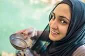 stock photo of middle eastern culture  - Arabic Muslim Middle Eastern girl drinking clean water on the river spring - JPG