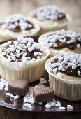 stock photo of chocolate muffin  - Muffins with chocolate icing with sugar grains and chocolates in a heart - JPG