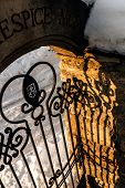 image of old stone fence  - Reflection of the sunset from the lattice gate carved on a stone fence - JPG