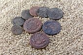 stock photo of copper coins  - nine old copper coins on river sand - JPG