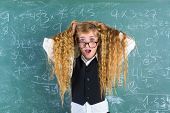 image of nerd  - Crazy nerd blond student girl holding hair surprised expression in green chalk board - JPG