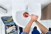 picture of plumber  - High Angle View Of Male Plumber Using Plunger In Bathroom Sink