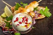 picture of kebab  - sauce chicken kebabs with pomegranate seeds on a background Chicken kebabs on a wooden dark background - JPG