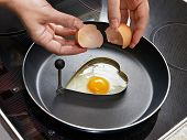 picture of yoke  - Woman preparing fried eggs in heart form for breakfast - JPG