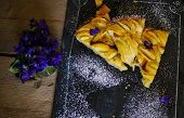 foto of helleborus  - French apple tart on the old rustic table with flowers and napkin - JPG