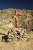 image of arid  - Christian cross wrapped around with flowers on peruvian arid landscape near Canon del Colca - JPG