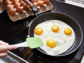 stock photo of fat cell  - Fried eggs close up on glass ceramic stove and packing eggs - JPG
