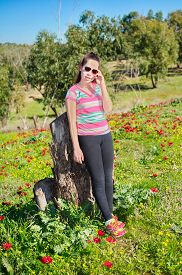 image of windflowers  - Teenage girl with braces on her teeth in a field of wild red anemone coronaria (windflower) flowers blooming in the Galilee Israel after the winter rains ** Note: Soft Focus at 100%, best at smaller sizes - JPG