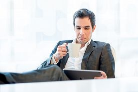 stock photo of disgusting  - Businessman relaxing with his feet up and a mug of coffee grimacing in disgust as he reads information or looks at a presentation on his tablet computer - JPG