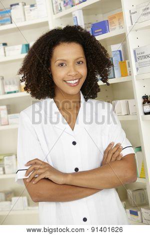 Female nurse standing in UK pharmacy