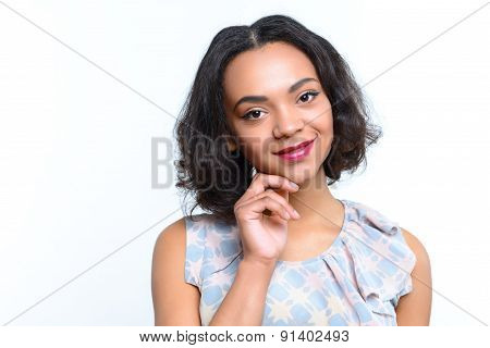 Mulatto girl touching her chin with fingers