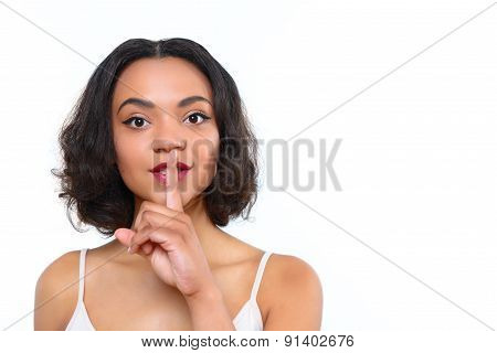 Mulatto girl with index finger on her mouth
