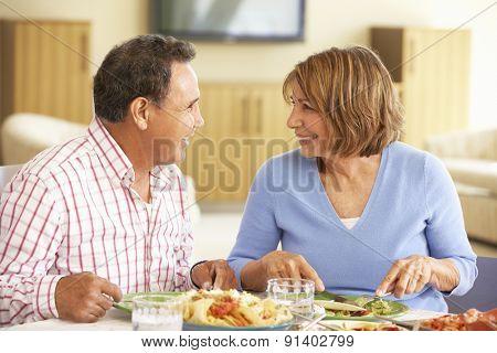Senior Hispanic Couple Enjoying Meal At Home