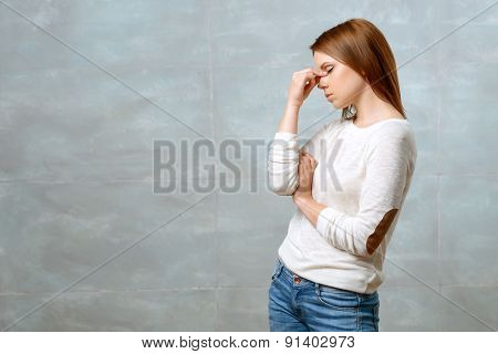 Woman standing and touching bridge of her nose