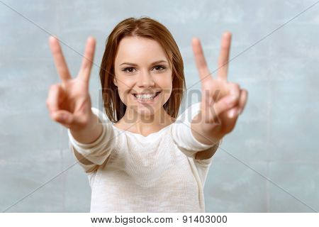 Smiling young woman showing two fingers