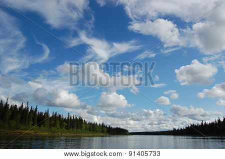 Clouds in the sky above the taiga river.