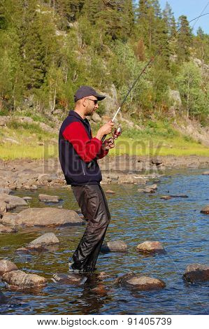 Fisherman catches a salmon in the north river.