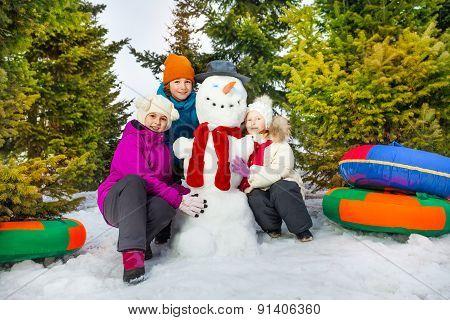 Happy children sitting close to cheerful snowman