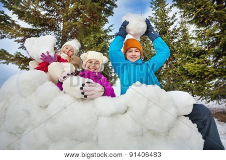Group of happy children hold snowballs to play