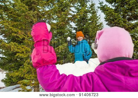 Girl holding snowball during game with boy