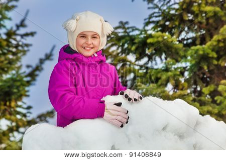 Portrait of a girl behind the snow wall in forest