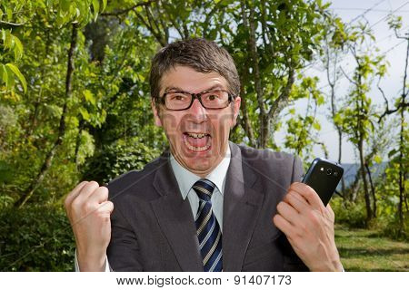 Happy businessman winning outdoor with mobile phone