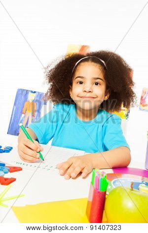 Cute African girl writing letters with pencil