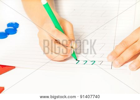 Close-up view of kids hands writing letters