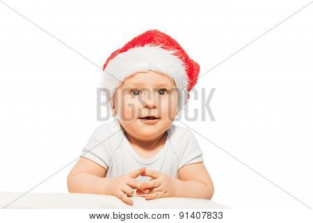 Sweet baby in red Christmas hat stands looking