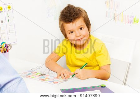 Smiling small boy coloring the shapes on paper