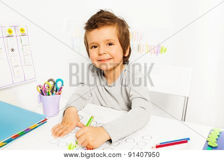 Positive small boy draws with pencil during ABA