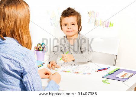Smiling small boy holds pencil and fill shapes