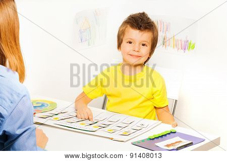 Smiling boy plays in game learn days of the week