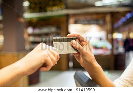 sale, shopping, payment, consumerism and people concept - close up of hands giving credit card at checkout in market or mall
