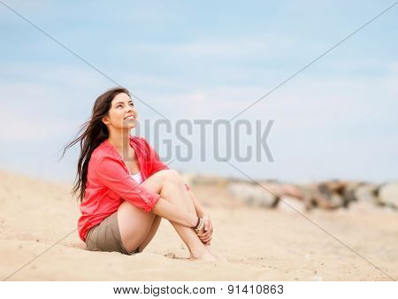 summer holidays and vacation - girl sitting on the beach