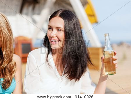 summer holidays and vacation - girl with drink and friends on the beach