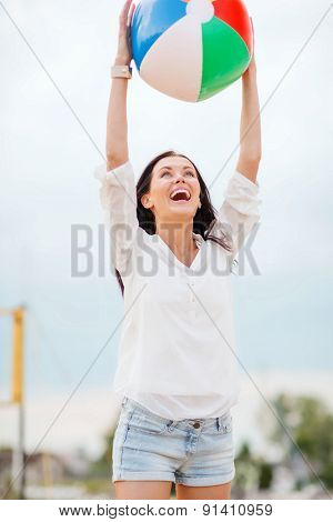 summer holidays, vacation and beach activities - girl playing ball on the beach
