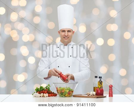 profession, vegetarian, food and people concept - happy male chef cooking and seasoning vegetable salad over christmas holidays lights background