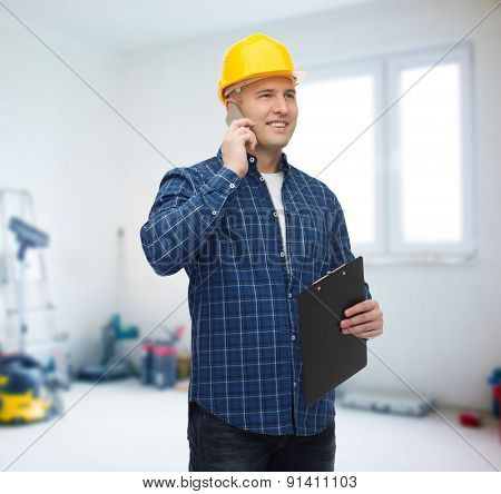 construction, building, people, technology and maintenance concept - smiling male builder or manual worker in helmet with clipboard calling on smarphone over room with work equipment background