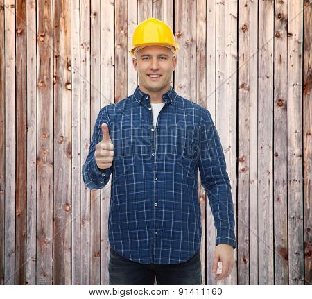 repair, construction, building, people and maintenance concept - smiling male builder or manual worker in helmet showing thumbs up over wooden fence background