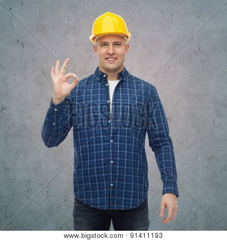 repair, construction, building, people and maintenance concept - smiling male builder or manual worker in helmet showing ok sign over gray concrete wall background