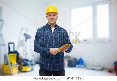 repair, building, construction and maintenance concept - smiling man in helmet with gloves over storeroom background